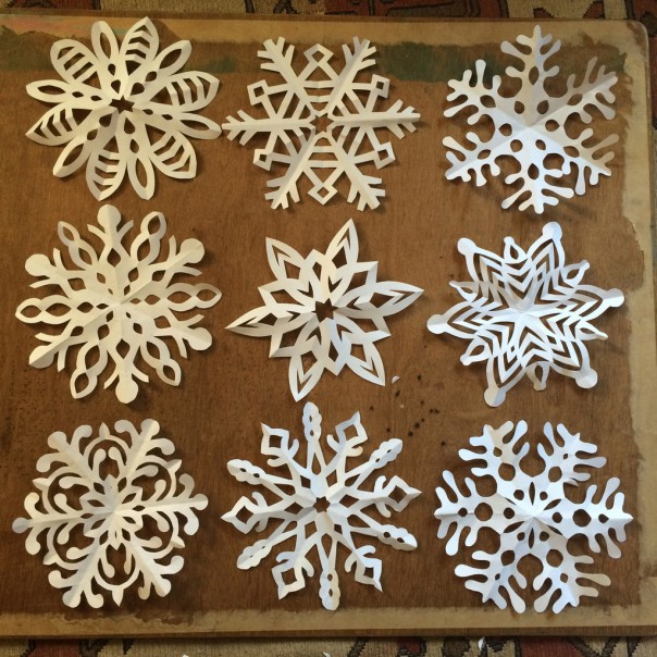 I design the snowflakes the traditional way with paper and scissors.