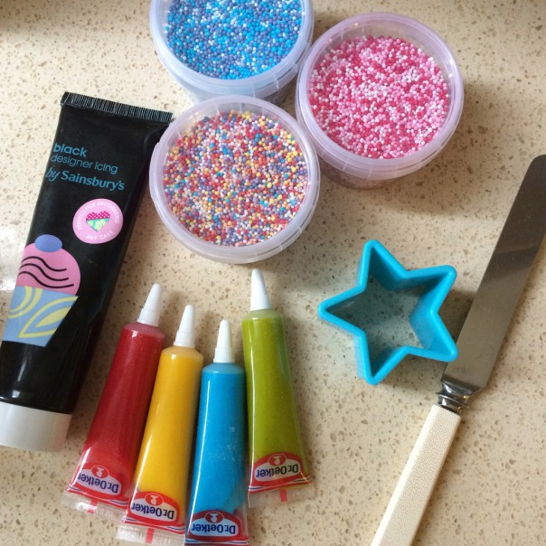 Decorating supplies: icing tubes, sprinkles, cookie cutter and a knife for spreading.