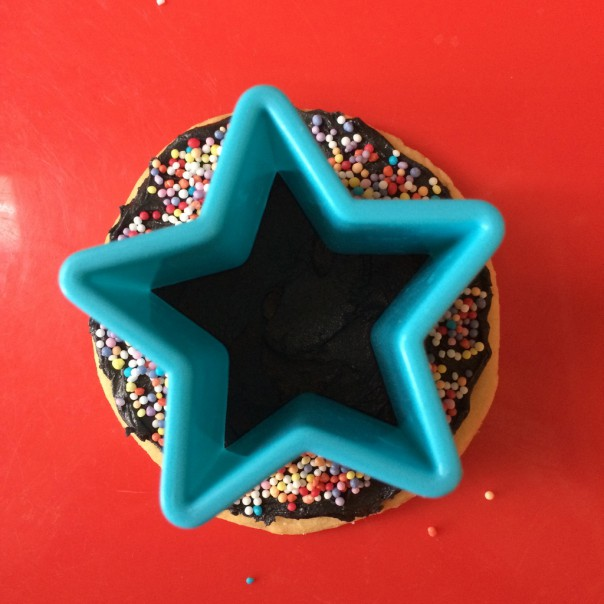 Place the cookie cutter lightly on the icing. Put sprinkles around the edges to create a negative pattern or inside to make a sprinkly star.