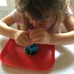 The girl decorating her cookie using a cookie cutter as a template.