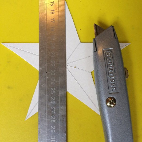Draw lines from point to opposite side with a pencil then using a ruler and knife, score over the lines very lightly (be careful not to press through too hard or your star will fall apart).