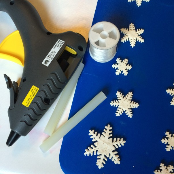 To make a snowflake hanging garland you'll need dried play clay shapes, a glue gun and fishing wire or invisible thread.