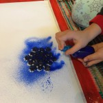 Lay out a large piece of paper on a messy mat. Place a stencil on the paper and spray the paint on top.