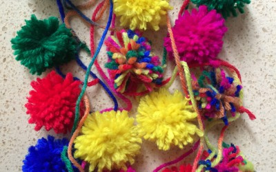 Attach lots of pom poms to a long piece of wool to make a pom pom garland.