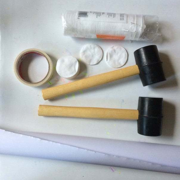 Poster roll, rubber mallets, masking tape and cotton wool pads.
