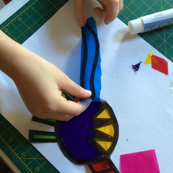 The girl adding colour to her diplodocus. Glue on the black card and stick pieces of acetate over the top. This doesn't need to be accurate - trim the excess afterwards.