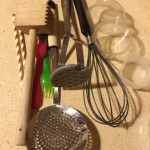 Drinking straws, wooden tenderiser, plastic forks, strainer, potato masher, whisk and plastic containers.