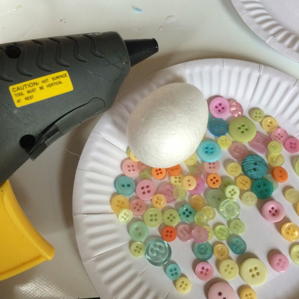 Button egg: buttons and glue gun. Glue gun buttons to the egg.
