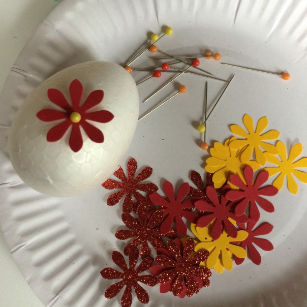 Paper punch egg: paper punched thin card and pins. Cut out shapes from coloured thin card with a paper punch. Pin in place all over the egg with plastic headed pins.