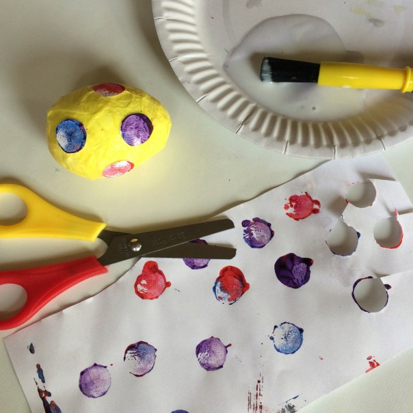 Spotty egg: tissue paper, decorated paper cut outs, PVA glue and a paintbrush. Cover the egg in glue and lay strips of tissue paper over until covered. Cut out decorated paper shapes and glue on top. Leave to dry.