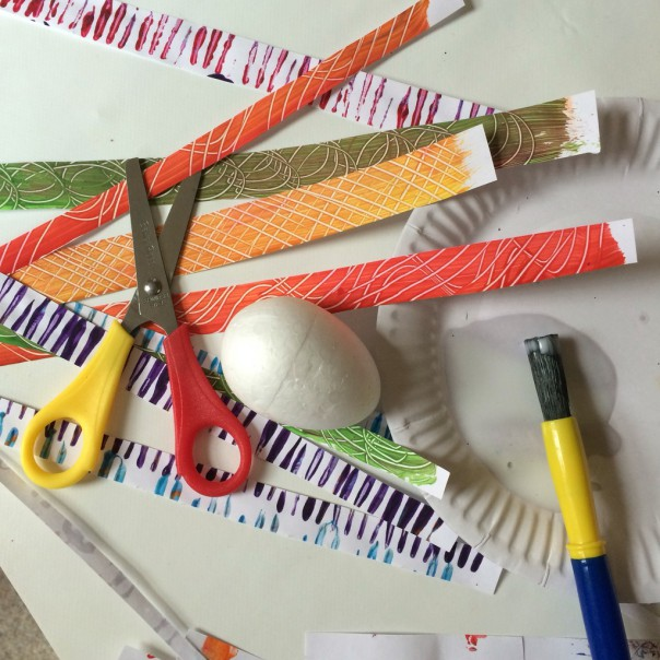 Paper egg: decorated paper strips, scissors, PVA glue and a paintbrush. Glue strips of decorated paper around the egg.