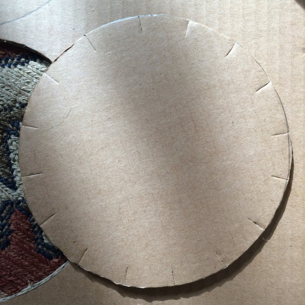 Make small cuts around the edge of the cardboard circle.