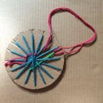 Thread a different coloured yarn on a wide eyed needle and start weaving through alternate spokes of the wheel.