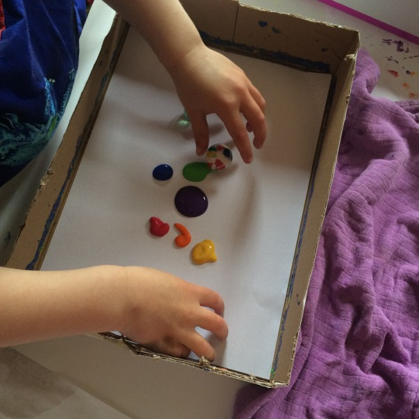 Drop dollops of paint onto your paper lined box or tray and place the balls into the paint.