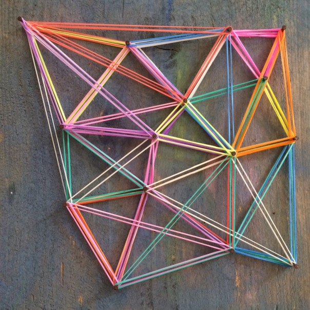 The boy made triangles with his loom bands.