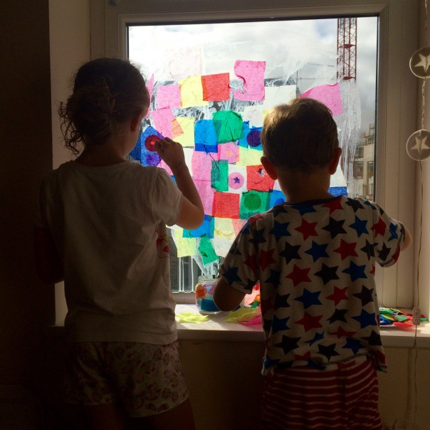 Paint the window with a layer of the glue and water mix and layer the tissue paper over the top.