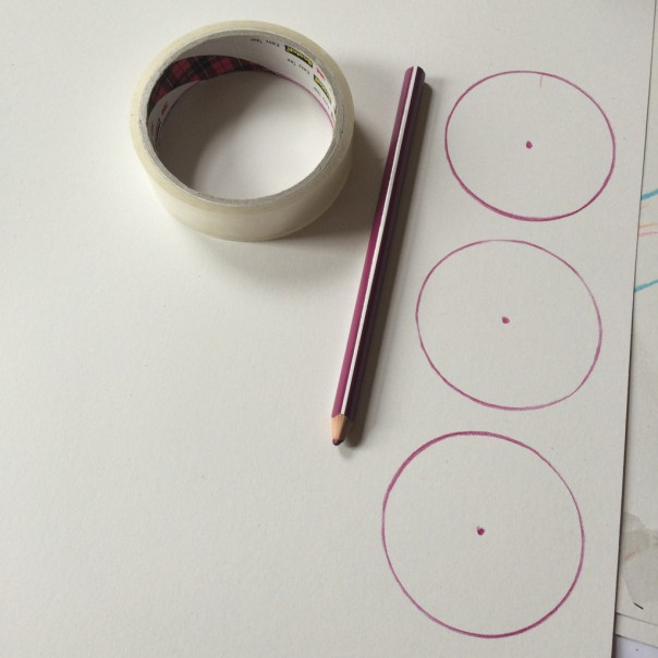 Draw circles on white card and poke a hole through the middle.