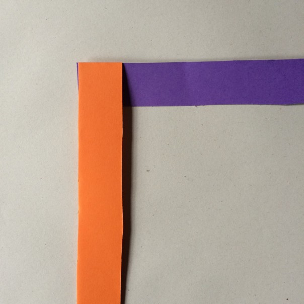 Fold one strip over the other, keeping the 'L' shape.